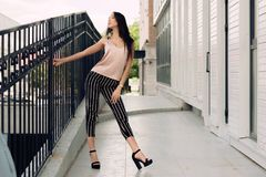 Beautiful young woman standing at the entrance to the underground garage. The model wears stylish clothes, a beige. Jersey, and black breeches in a white stripe Royalty Free Stock Image