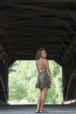 Beautiful young woman standing in front of covered bridge - summer Stock Images
