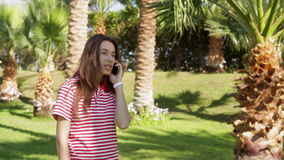 Beautiful young woman standing on a green lawn and talking on phone stock video footage