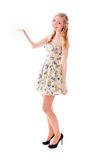 Beautiful young woman standing with her arm outstretched Stock Photo