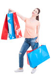 Beautiful young woman standing and holding shopping bags feeling Royalty Free Stock Photography