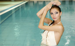 Beautiful Young Woman Standing In A Swimming Pool Royalty Free Stock Photos