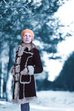 Beautiful young woman standing looks away wearing brown coat beret hat in winter cold snowy scandinavian forest Royalty Free Stock Photo