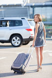 Beautiful young woman is standing near the airport. Attractive girl is going to her car. She is holding a suitcase and enjoying her trip. The lady is looking Stock Images