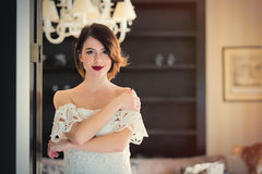 beautiful young woman standing near the door in the light Stock Photos