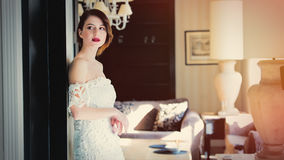 Beautiful young woman standing near the door in the light luxury Stock Image