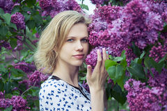 Beautiful young woman standing near lilac. And smile royalty free stock images