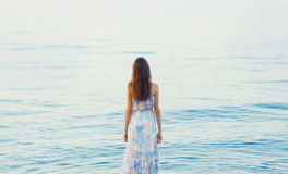 Beautiful young woman standing near sea, back female Stock Images