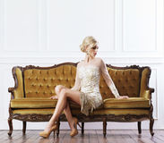 Beautiful, young woman standing near a sofa Royalty Free Stock Images