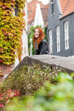 Beautiful young woman standing near the stone fence and explorin. G the town Royalty Free Stock Images