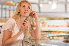 Beautiful young woman standing near supermarket showcase. Full of different products and deciding what to buy Royalty Free Stock Photography