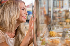 Beautiful young woman standing near supermarket showcase. Full of different products and showing how she wants something royalty free stock image