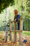 Beautiful young woman standing near wooden fence with bicycle in Royalty Free Stock Photography