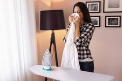 Woman smelling clean shirt. Beautiful young woman standing next to an ironing board, smelling fresh, clean shirt royalty free stock images