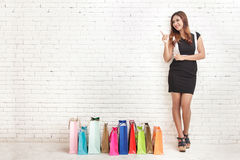 Beautiful young woman standing next to shopping bags while point. Full body portrait of beautiful young woman standing next to shopping bags while pointing at Royalty Free Stock Image