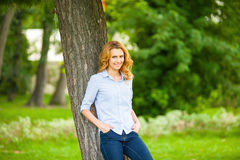 Beautiful young woman standing next to a tree Stock Images