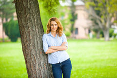 Beautiful young woman standing next to a tree Royalty Free Stock Images