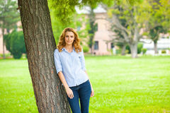 Beautiful young woman standing next to a tree Royalty Free Stock Image