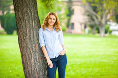 Beautiful young woman standing next to a tree Royalty Free Stock Photos