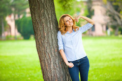 Beautiful young woman standing next to a tree Stock Photo