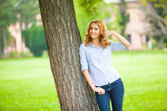 Beautiful young woman standing next to a tree Stock Photos