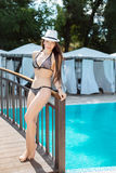 Beautiful young woman standing at a pool Royalty Free Stock Photo