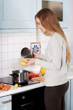 Beautiful young woman standing and preparing food. Royalty Free Stock Image