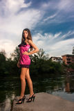 Beautiful young woman standing by the river Stock Photos