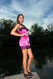 Beautiful young woman standing by the river Stock Photography