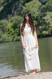 Beautiful young woman standing on the side of a river Royalty Free Stock Images