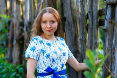 Beautiful young woman standing with a smile. Portrait of a beautiful girl in white dress among trees in the forest. Girl. Royalty Free Stock Photo