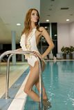Beautiful young woman standing in a swimming pool Royalty Free Stock Images