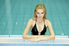 Beautiful young woman standing in a swimming pool Stock Images