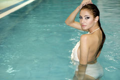 Beautiful young woman standing in a swimming pool Stock Photos