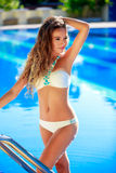 Beautiful young woman standing in a swimming pool Royalty Free Stock Photo