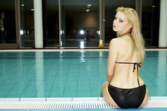 Beautiful young woman standing in a swimming pool Stock Photography