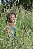 Beautiful young woman standing in tall grass - rural summer Royalty Free Stock Photography
