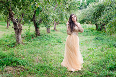 Beautiful young woman is standing between the trees Royalty Free Stock Photo