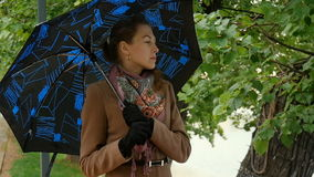 Beautiful young woman standing under an umbrella. stock footage