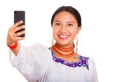 Beautiful young woman standing wearing traditional andean blouse and red necklace, holding mobile phone taking selfie Royalty Free Stock Images