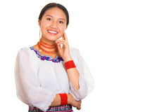 Beautiful young woman standing wearing traditional andean blouse and red necklace, resting head on hand while smiling Stock Image