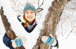 Beautiful young woman stands behind snowy tree in winter park Stock Photos