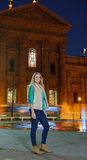 Beautiful young woman stands in front of cityscape at night Stock Photos
