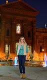 Beautiful young woman stands in front of cityscape at night Stock Images
