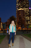 Beautiful young woman stands in front of cityscape at night Royalty Free Stock Image
