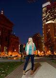 Beautiful young woman stands in front of cityscape at night Royalty Free Stock Photos