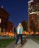 Beautiful young woman stands in front of cityscape at night Stock Photo