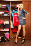 Beautiful young woman stands near her wardrobe  in different sho Royalty Free Stock Image