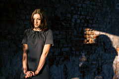 Beautiful young woman stands near the old brick wall Stock Image