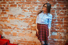 Beautiful young woman stands near the old brick wall. Youth styl Stock Photography